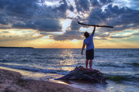 Promise of a New Day  Teenaged male standing on the beach greeting the new day with enthusiasm  Port Crescent State Park  Port Austin, Michigan  版權商用圖片
