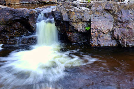 Relaxing cascade flowing into the refreshing pool below  Big Erics Falls State Forest  Baraga, Michigan  photo