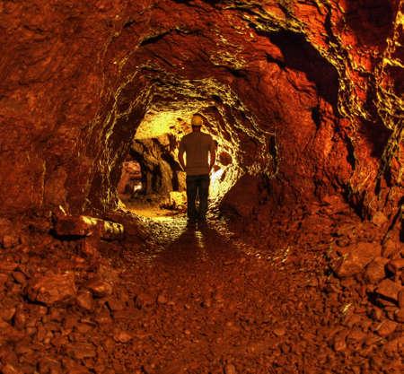 the miner: Life Underground  Man in a miner hat, exploring the caverns of the abandoned Delaware Copper Mine  Now a part of the Keewenaw National Historic Park   Stock Photo
