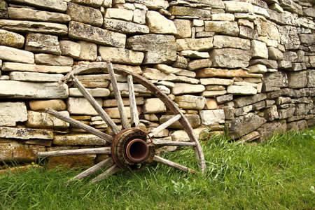 Broken  Antique wagon wheel with historic stone wall in the background  Fayette State Park  Fayette, Michigan  photo