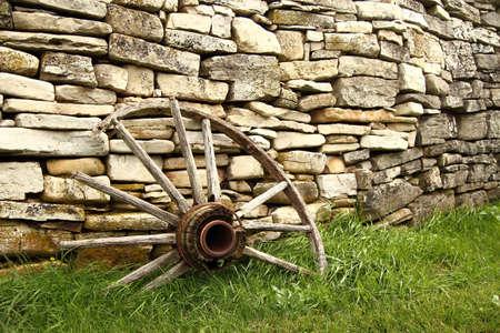 Gebroken Antieke wagenwiel met historische stenen muur op de achtergrond Fayette State Park Fayette, Michigan