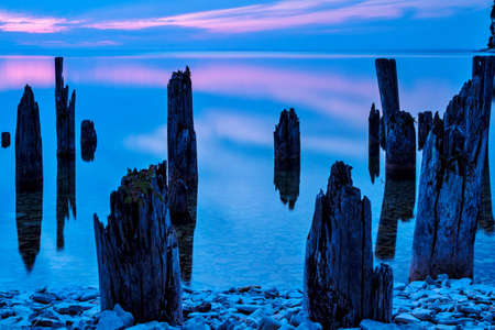 Ghosts  Remnants of an abandoned pier at dusk, with the placid waters of Lake Michigan as a background  Fayette State Park  Fayette, Michigan