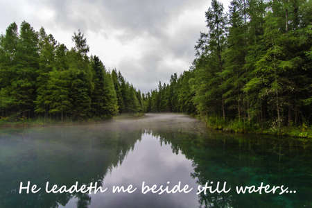 verse: Mist shrouded river throught the woods with biblical verse  Stock Photo