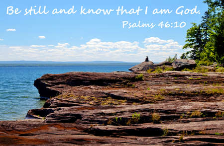 Man on cliff overlooking Lake Superior with quote,  Be still and know that I am God   photo