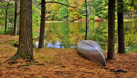 ludington: Autumn Paradise  Canoe at the waters edge with autumn foliage reflections on Lost Lake  Ludington State Park  Ludington, Michigan
