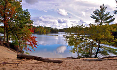ludington: Hamlin Lake Overlook  Gorgeous blue sky reflections, fall colors and a park bench nestled at the bottom of a sand dune  Ludington State Park  Ludington, Michigan  Stock Photo