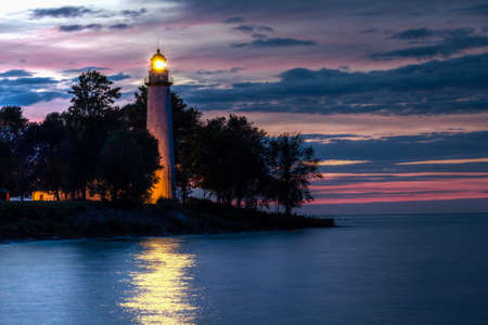 Point Aux Barques Lighthouse beacon shines over the waters of Lake Huron,  warning  sailors of the impending perils that lie just under the surface of the decptively calm waters  Lighthouse County Park  Port Hope, Michigan   photo