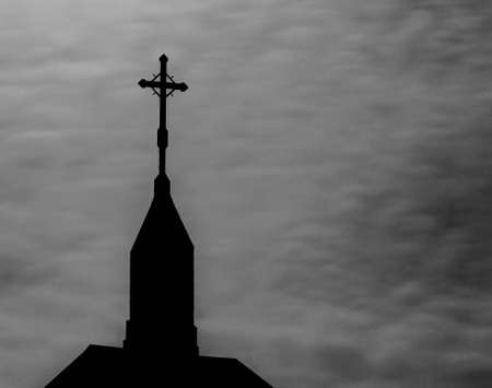Celtic cross on a steeple set against stormy grey skies photo