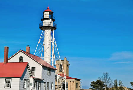 Whitefish Point lighthouse stands guard on the isolated Lake Superior shoreline  This shoreline is notoriously dangerous and due to so many shipwrecks is referred to as the Graveyard Coast  Great Lakes Shipwreck Museum  Whitefish Point, Michigan  photo
