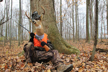 trofeo: Venganza Ocho punto buck en su totalidad el camuflaje, la celebración de una espera de escopeta para el cazador desventurado a vagar por Foto de archivo