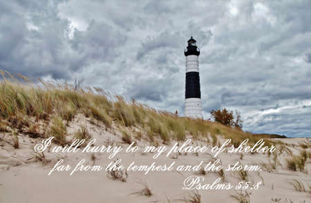 Lighthouse standing on a windswept shore, with stormy skies overhead  Includes the following scripture from the old testament,  I will hurry to my place of shelter, far from the tempest and the storm   Psalms 55 8  The Big Sable Lighthouse is located in L Stock Photo