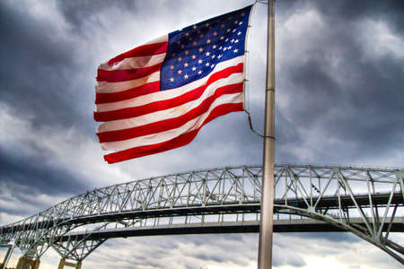 Old glory stands guard over an international border crossing.  The contains the Blue Water Bridges, which are the second busiest border crossing between the United States and Canada   The Blue Water Bridges connect the communities of Port Huron, photo