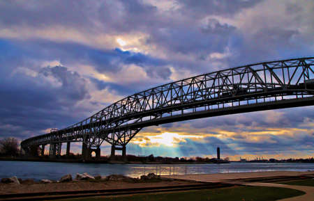 Good Morning Ontario  Beams of light illuminate the Canadian shore with the Blue Water Bridges in the foreground  This is the second busiest Canadian American border crossing   photo