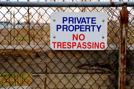 trespassing: Private Property  Chain link fence with colorful No Trespassing sign
