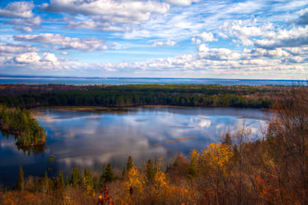 upper peninsula: Sweeping panoramic view of an inland lake with blue sky reflections and the great waters of Lake Superior at the horizon   Spectacle Lake Overlook   Brimley, Michigan