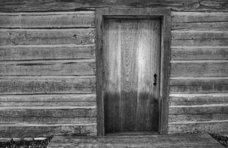 Black and white close up of the front porch of a historic pioneer log cabin  Goodells County Park  St  Clair County, Michigan  photo