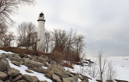 Pt  Aux Barques Lighthouse stands guard on the rocky winter shoreline  Ligthouse County Park  Port Hope, Michigan   photo