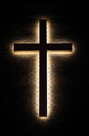 sacred trinity: The Light  Illuminated cross on a brick wall background