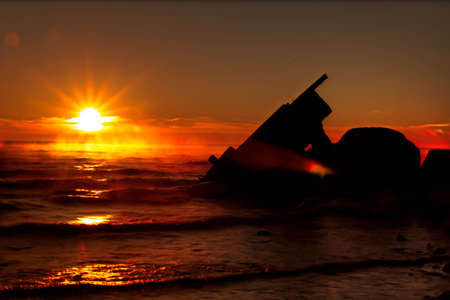 huron: Shipwreck Dawn  Sun rises over a misty Lake Huron with the silhouette of a shipwreck in the foreground