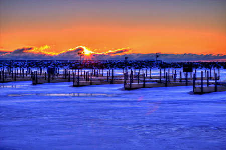 shanty: Ice Fishermen enjoy a Great Lakes sunrise from the comfort of their shanty  Lexington State Harbor  Lexington, Michigan  Stock Photo