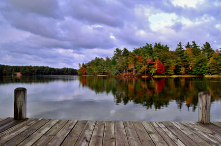 michigan: A Day At The Lake  Wooden dock overlooking a lake and an island ablaze in fall splendor  Ludington State Park  Ludington, Michigan