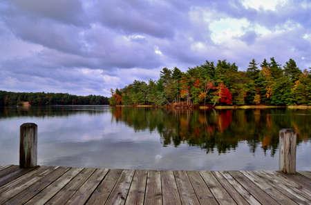 Un día en el muelle de madera lago con vistas a un lago y una isla en llamas en su esplendor caída Ludington State Park Ludington, Michigan