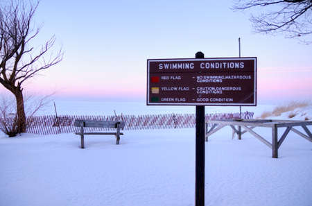 michigan snow: Great Day For A Swim  Great Lakes coast encased in snow and ice and a sign informing of the swimming conditions  Port Crescent State Park  Port Austin, Michigan   Stock Photo
