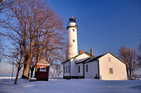 Beautiful Point Aux Barques Lighthouse bathed in the warmth of the afternoon sun, on a cold winters day  Lighthouse Park  Port Hope, Michigan   photo