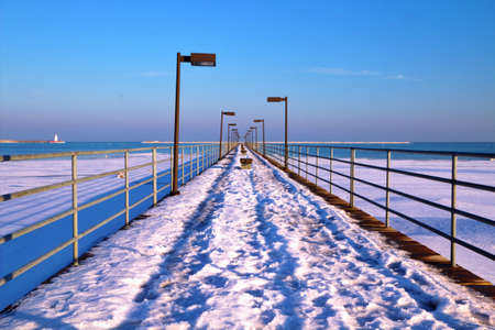 Winter Walk  A snow covered pier extends into the wintry Great Lakes horizon  Harbor Beach, Michigan   photo