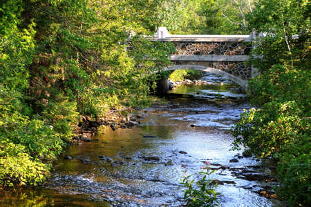 Vrede Stenen brug en kabbelende beek stroomt richting de machtige Lake Superior Fort Wilkins State Park Copper Harbor, Michigan