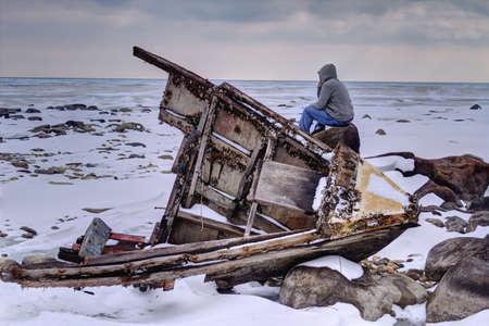 Schipbreukelingen Teenaged mannetje dat een bevroren Lake Huron met houten romp van een scheepswrak op de voorgrond Sanilac County Park Lexington, Michigan Stockfoto