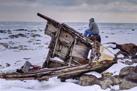 Shipwrecked  Teenaged male looking a frozen Lake Huron with wooden hull of a shipwreck in the foreground  Sanilac County Park  Lexington, Michigan   Stock Photo