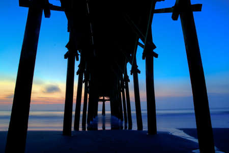 Pier at sunset with a silhouette of a cross back lit by the sunset sky   photo