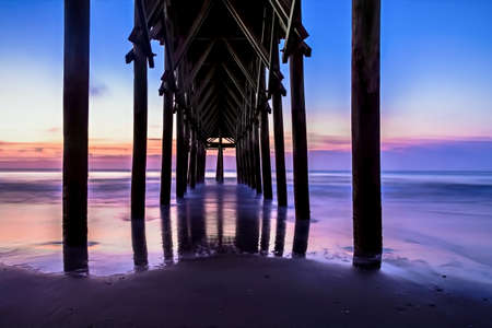 endings: Gorgeous sunrise background from underneath a coastal pier with a silhouette of a cross in the background   Stock Photo