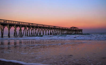 Myrtle Beach State Park pier jutting into the Atlantic Ocean with a sunset sky background  Myrtle Beach, South Carolina