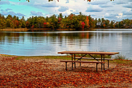ludington: Picnic table on the shore of Lost Lake with fall foliage as the backdrop  Ludington State Park  Ludington, Michigan  Stock Photo
