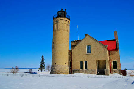 Winter at the Old Mackinac Point Lighthouse with the Mackinaw Bridge as the backdrop  Mackinaw City, Michigan photo