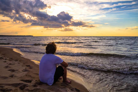 Teenaged boy watching the sunset over the ocean horizon  Stock Photo