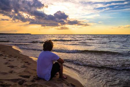 Tienerjongen kijken naar de zonsondergang over de oceaan horizon
