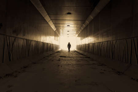 tunel: Stranger Danger Silueta de un hombre que espera en la final de un callejón oscuro Foto de archivo