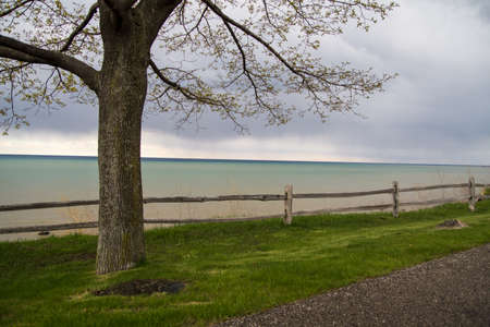 drop off: Split rail fence acts as a boundary between a park and a dangerous drop off to Lake Huron