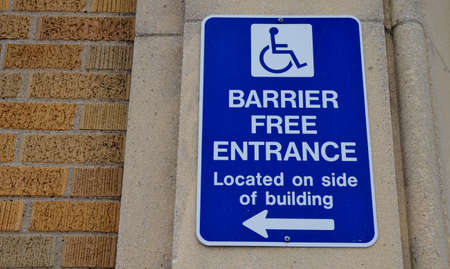 Barrier free entrance sign on brick building  photo