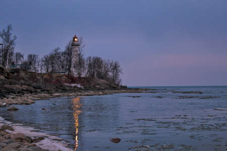 The Pt  Aux Barques lighthouse beacon shines along the lonely Lake Huron shore  Lighthouse Park  Port Hope, Michigan   photo