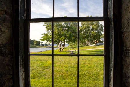 window view: Looking out the window of a century old farmhouse with a view of the lakeshore and field with wagon wheel   Fayette State Historical Park  Garden, Michigan  Stock Photo