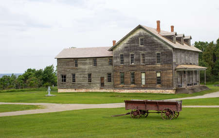 Century old farmhouse with vintage horse drawn wagon in the foreground  Fayette State Historical Park  Garden, Michigan