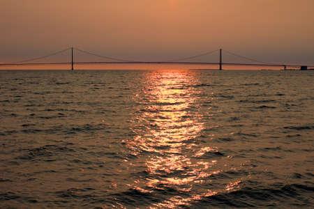 mackinac: Straits of Mackinac at sunset with the Mackinac Bridge at the horizon   Stock Photo