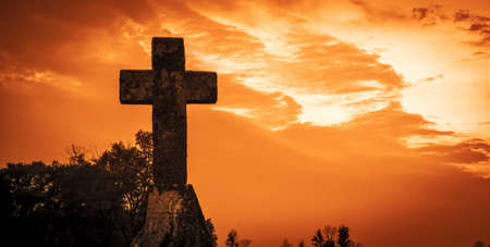 Silhouette of a cross against a red sky background   photo
