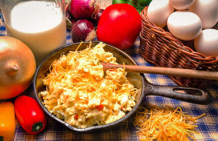 Cast Iron Skillet with western style scrambled eggs  Including onions, red peppers, cheese and tomato  Stock Photo
