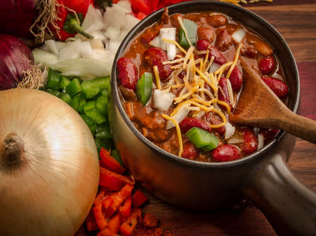 Spicy bowl of chili surrounded by fresh onion, green peppers, and red peppers