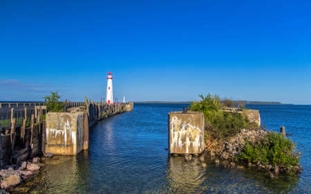 upper peninsula: Coastal Landscape. St. Ignace waterfront with historical dock and the Chief Wawatam Lighthouse.